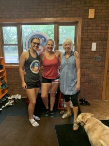 three women (one older, one middle age, one younger) stand in a gym entry way wearing work out clothing. a dog is in the foreground.